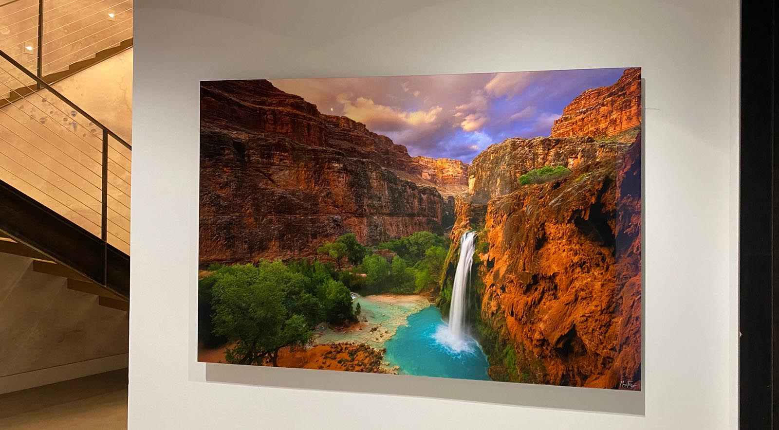 A 72 inch Gallery Ultra TruLife® Acrylic Print of Garden of Eden lit from above with angled recessed lights.